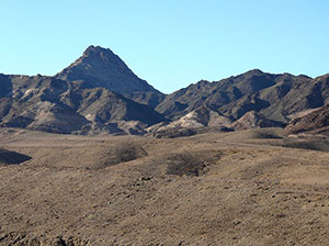 The panorama shows a harsh landscape of browns, blacks and reds.  There is no visible greenery among these mountains.
