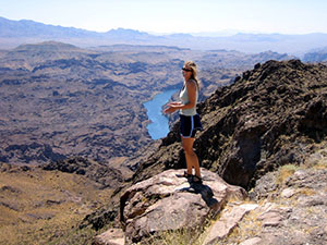 A woman stands overlooking a harsh, rocky, barren desert landscape, with a section of Lake Mohave far below.