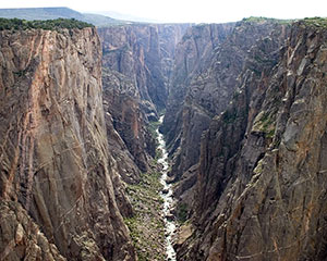 View looking up a steep-sided canyon with a river flowing at the bottom