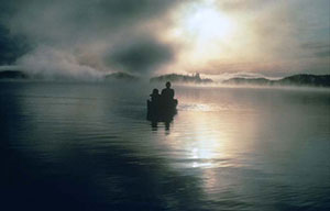A mystical scene of two people in a small canoe, silhouetted against placid morning waters. The sun casts a shadow on the silver water, reflecting off the surrounding fog.