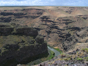 A nearly flat horizon gives way to steep stair step canyon walls with a river winding through the bottom.