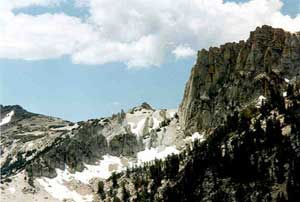 A rugged alpine landscape, snow stretching up to rocky faces above a steep forest slope.