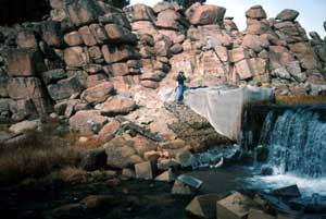A man standing near a waterfall, surrounded by natural piles of large textured rock.