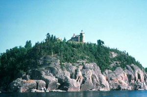 A small lighthouse along the coast at the top of a large rocky head, surrounded by small trees.
