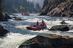 A raft carrying two people hits rapids