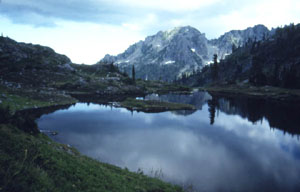 A moody image of a dark alpine lake reflecting brooding clouds high above, over a jagged rocky peak in the near distance.