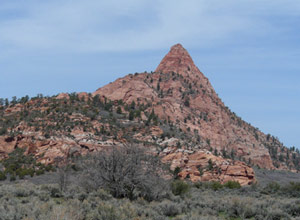 A crimson butte is the subject of this desert panorama.
