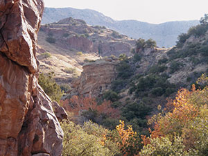 A large rock frames the left side view into a valley filled with Autumn vegetation