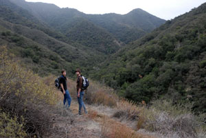 Two hikers standing along a trail, descending into a dense valley. Green vegetation covers the surrounding hills.