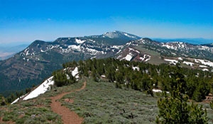 View of Eagle Peak and summit trail from the shoulder of Warren Peak. The photo captures the pine trees, grass, adn snow that populate the area.
