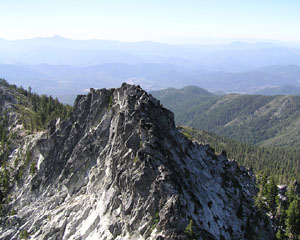 A view from atop of the summit of Monument Peak. The peak is free of trees and is composed of rock while the mountainside houses trees and other foliage.