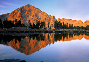 Sunset on mountains at the edge of a calm lake