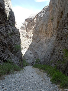 A hiker hikes down Arrow Canyon, a thin canyon with steep rock walls.