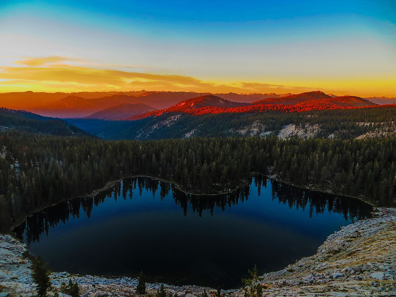 Sunset over mountains and a lake