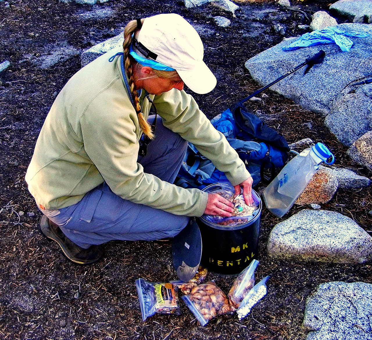 Woman packing a bear canister with food