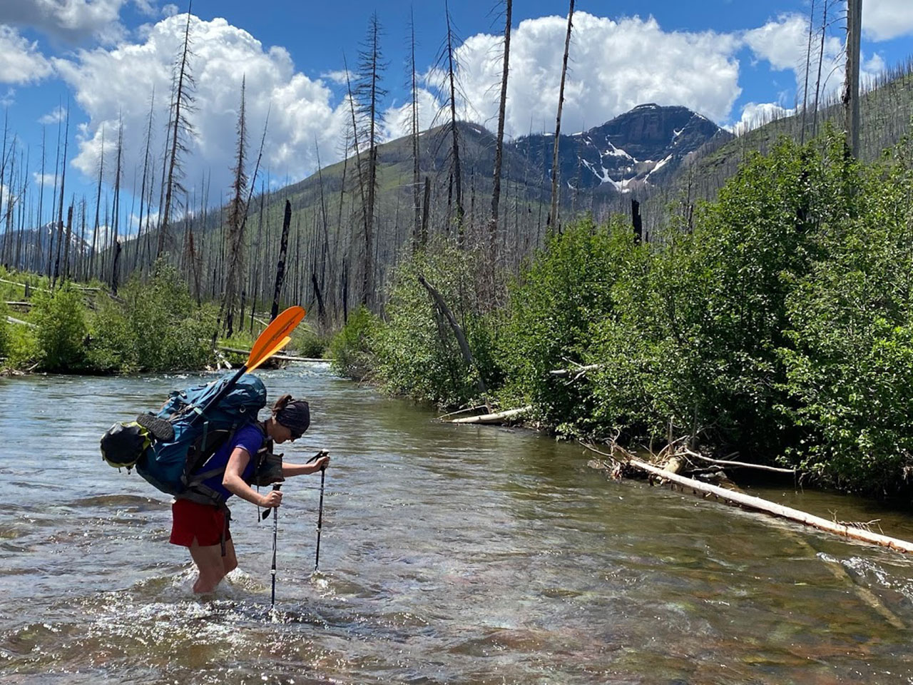 Backpacker crossing a creek
