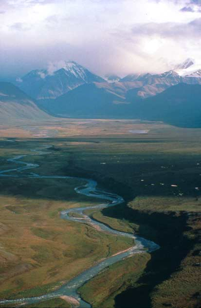An aerial view looking up a river flowing through a wide plane, towards massive Alaskan mountains shrouded in cloud.