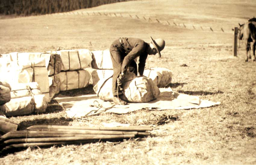 A vintage black and white image of a man in a cowboy hat, unloading supplies.