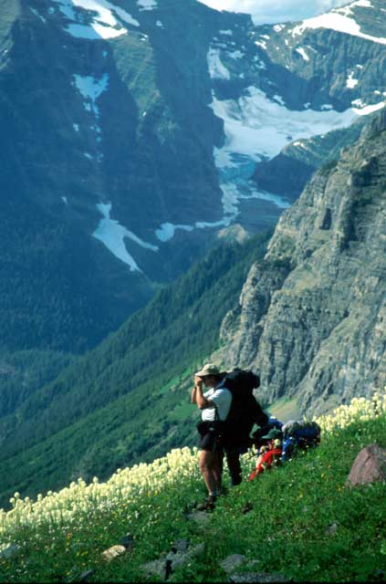 Two backpackers on a steep grassy slope, a background of vertical rock faces laced with glaciers and snow in the distance.