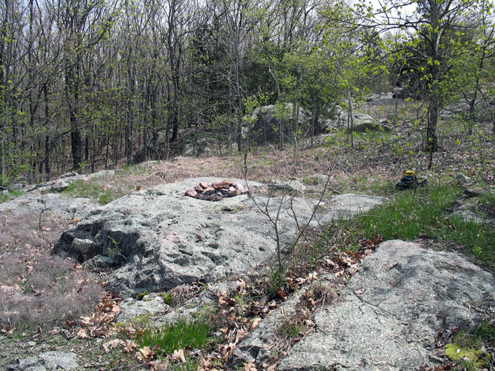 An old campsite set atop a small rock outcropping, surrounded by open woodland trees.