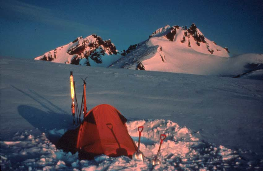 An iconic mountain scene of a small tent pitched amid the snow, looking up slope to rugged snow-covered peaks, drenched in rich evening light.