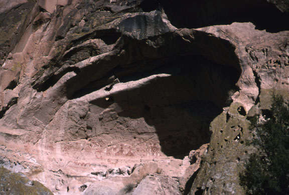 This is a photo of a painted cave. The cave is a large hole in a purple rock edifice.