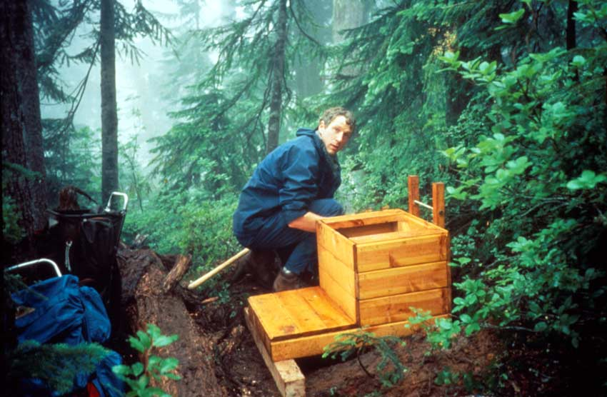 A man in a blue jacket standing next to a new backcountry toilet, surrounded by dense green forest undergrowth.