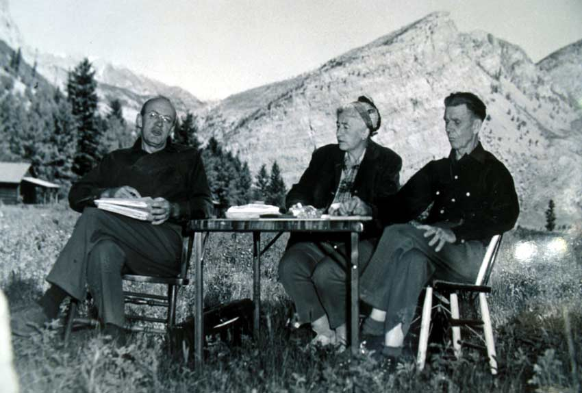 A vintage black and white image of three elderly people sitting around a table outside, with vertical rock faces in the background.