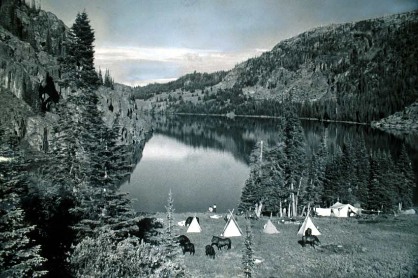 A vintage black and white image of a teepee camp near a placid lake, cradled in a small rocky valley.
