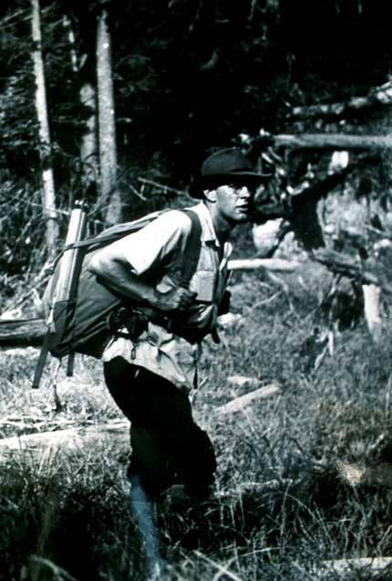 A vintage black and white image of a man walking through the forest with a large backpack.