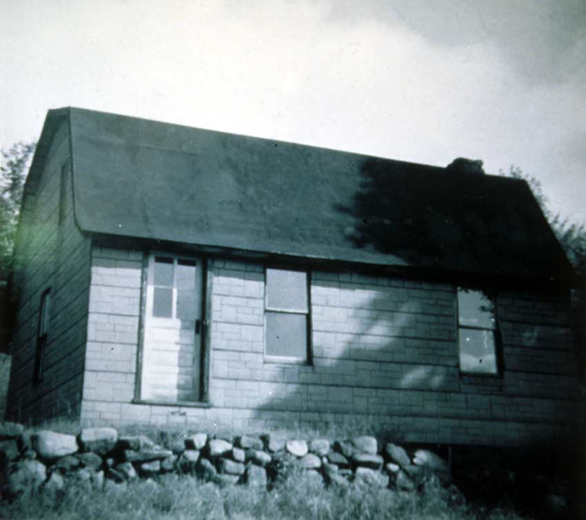 A vintage black and white image of a small brick house.