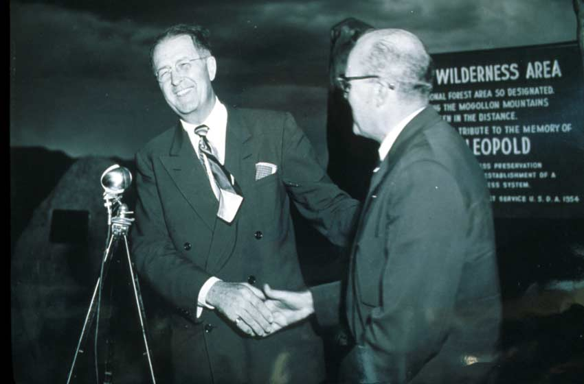 A vintage black and white image of two men shaking hands near a microphone.