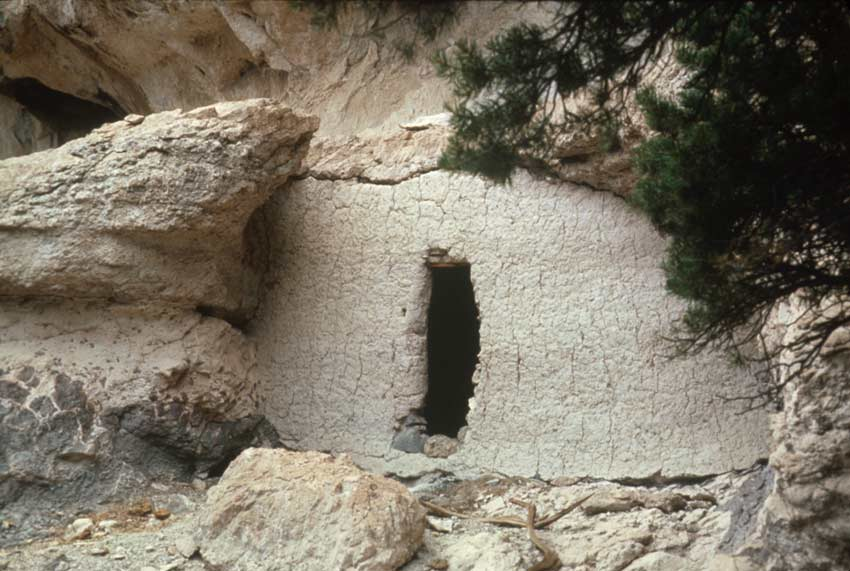 An ancient cave-like dwelling, along part of a rocky face.