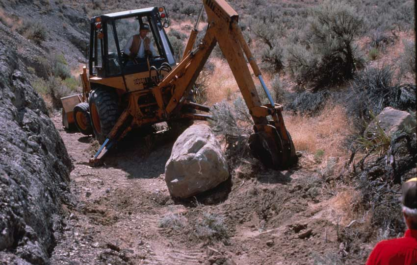 A yellow backhoe clearing a large boulder out of a small desert drainage.
