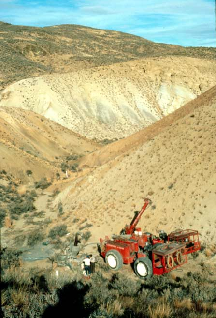 A large red piece of machinery near a sandy desert drainage.