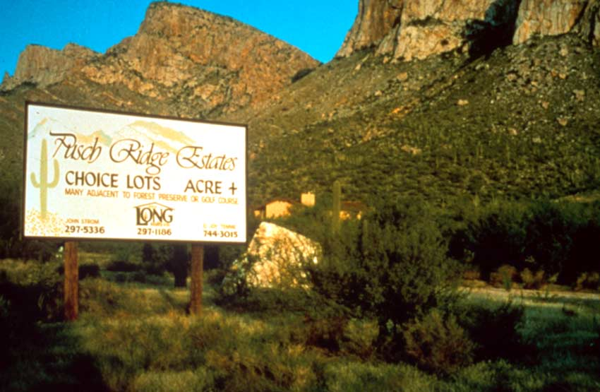 A large white billboard sign sitting in the desert, large desert cliffs rising in the background.