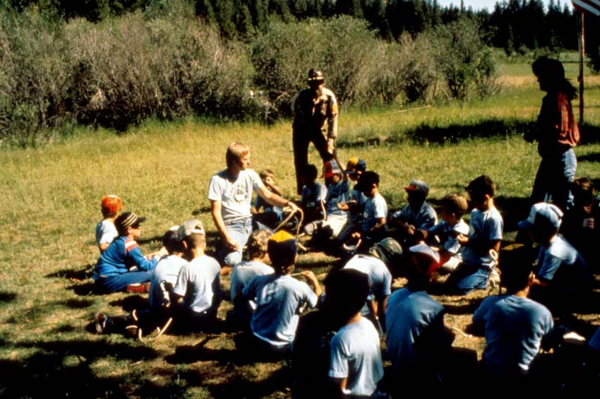 A Park ranger talking to a large group of young children gathered on the grass.