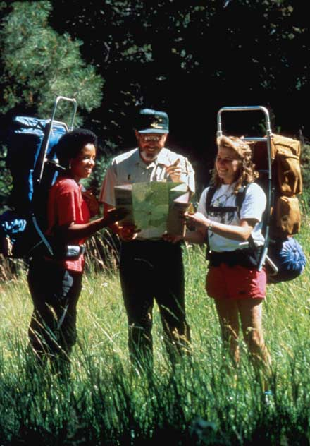 Two women with backpacks stand with a Park ranger, looking over a map.