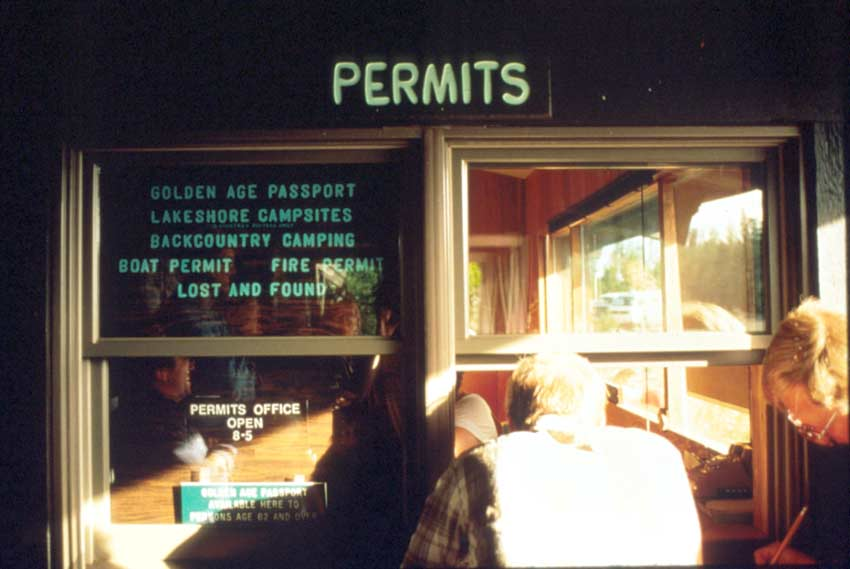 Looking into the window of a backcountry permit office, with several people gathered inside.