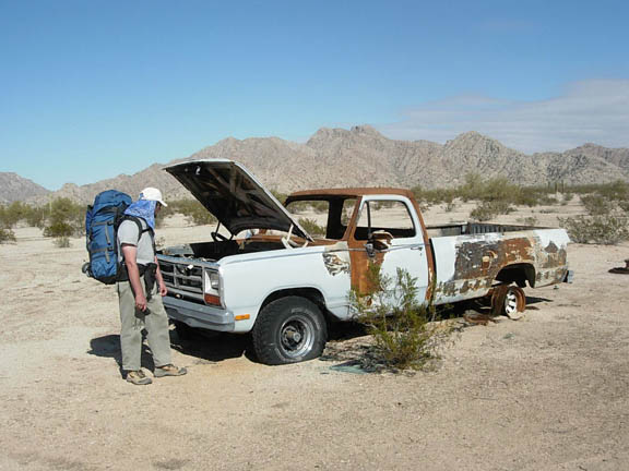 An abandoned truck in the middle of the desert. The truck used to be blue, but now is patched with rust and the back left tire is missing.