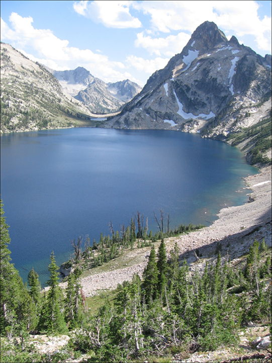 A large deep blue alpine lake sits at the base of steep rocky slopes with a snow patched mountain looming at the far end.
