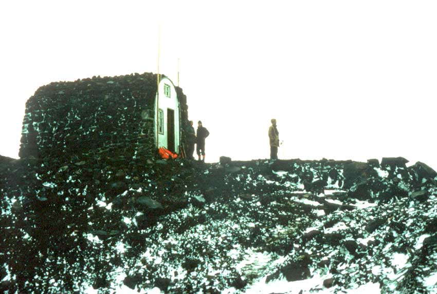 A small military-style hut on a rocky ridge, with three men standing outside on the snow covered rock, under a blank white sky.