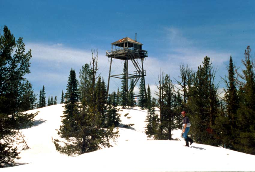 A person walking up a snow covered slope, to a tall fire lookout station at the top.