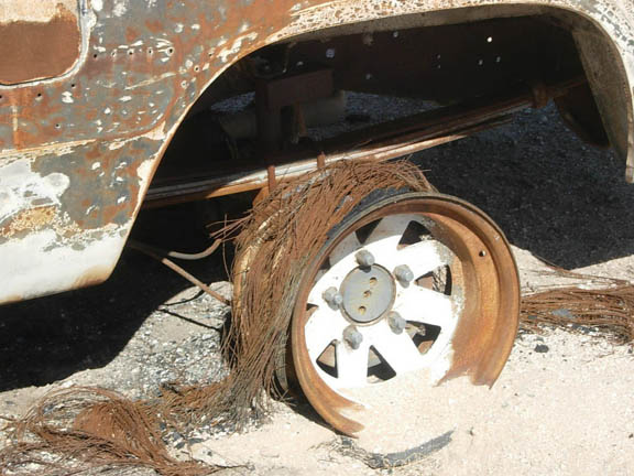 A desserted vehicle in the Cabeza Prieta Wilderness. The back tire has been burned away, leaving only the mount.