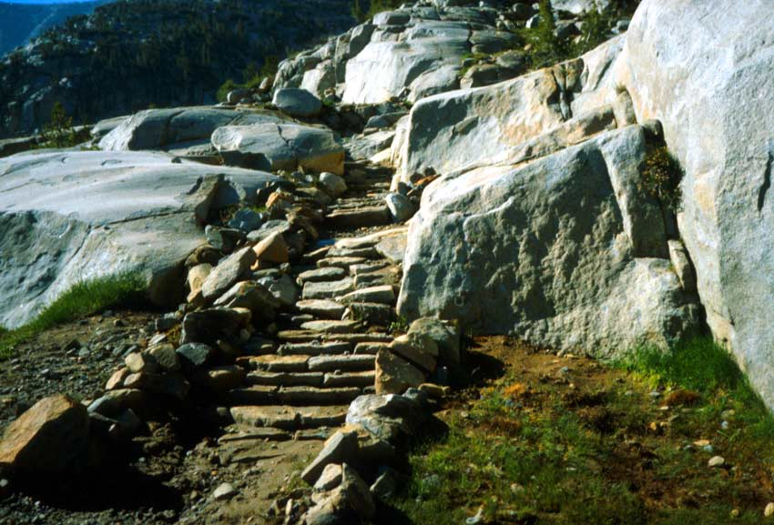 A small stone stairway, leading up a path through a rock outcropping.
