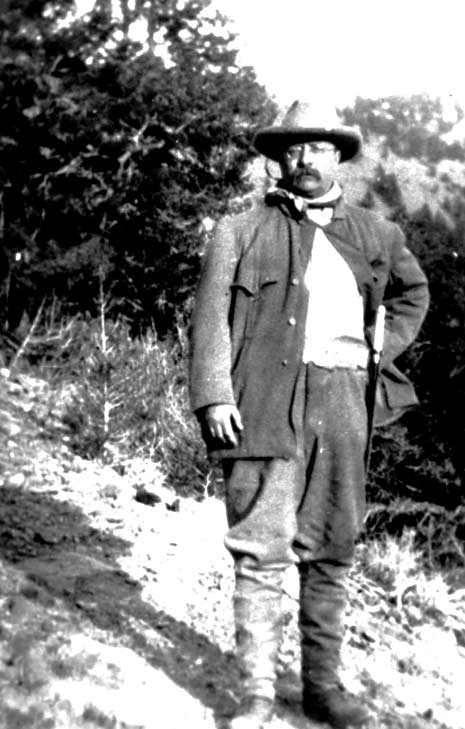 A vintage black and white image of Teddy Roosevelt in the outdoors.