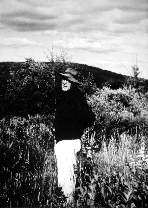 A vintage black and white image of a man standing in tall grass, with hills in the background.