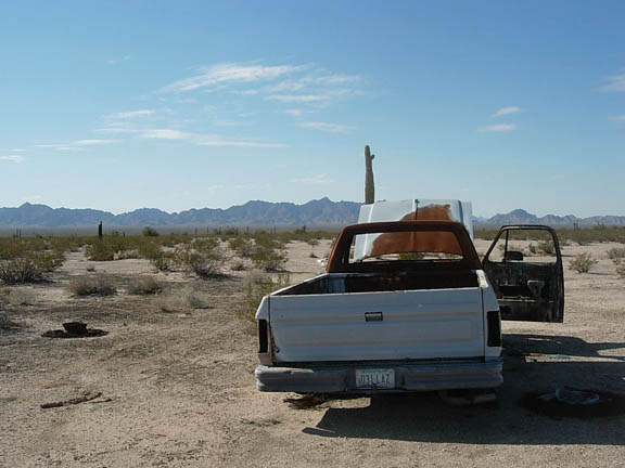 A rear-view of an abondoned truck in the middle of the Cabeza Prieta Wilderness. The truck has Arizona plates and sits idly in the middle of this vast wilderness.