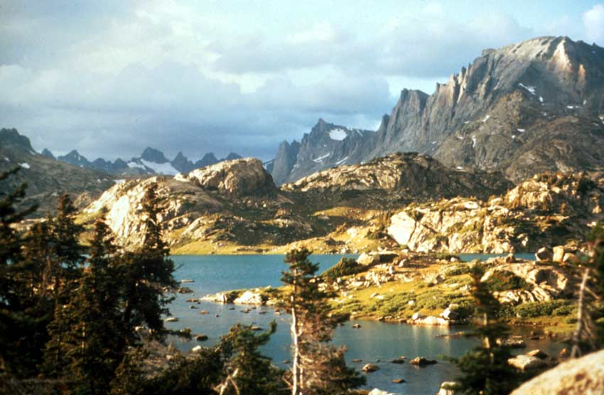An alpine lake surrounded by rocky meadow, bathed in evening light. Jagged mountain peaks rise in the distance, under a cloudy sky.