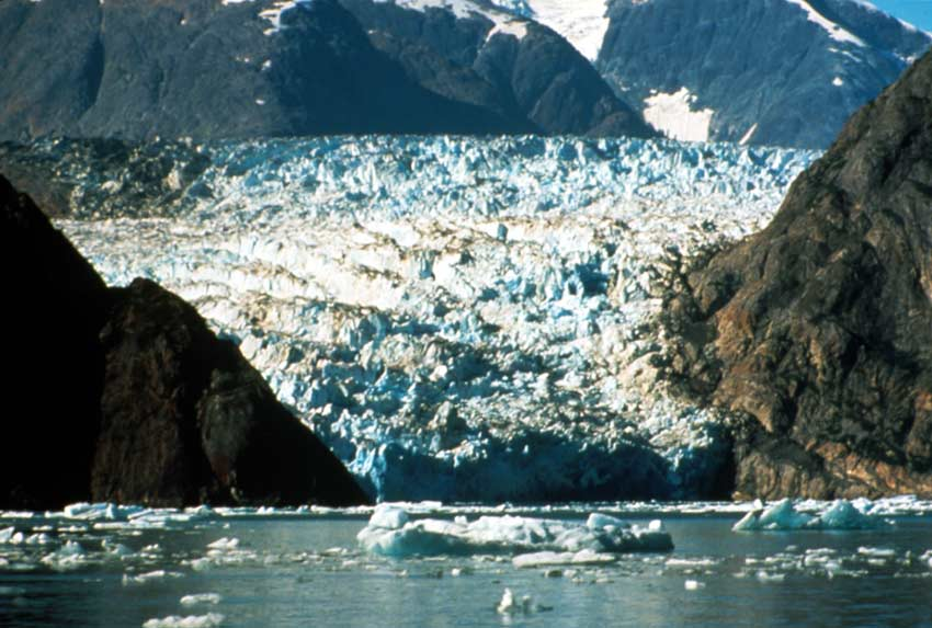A large tidewater glacier pouring out of a mountain valley, scoured rock walls funneling the fractured ice to the water.